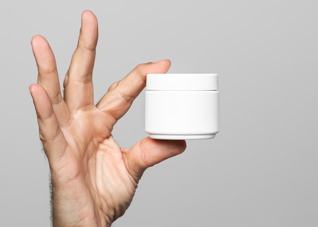 Zbliżenie dłoni trzymającej pojemnik kremu