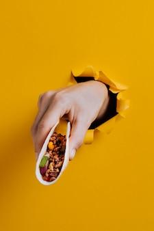Zbliżenie dłoni trzymającej pyszne taco