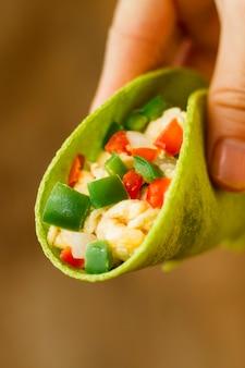 Zbliżenie dłoni trzymającej smaczne taco