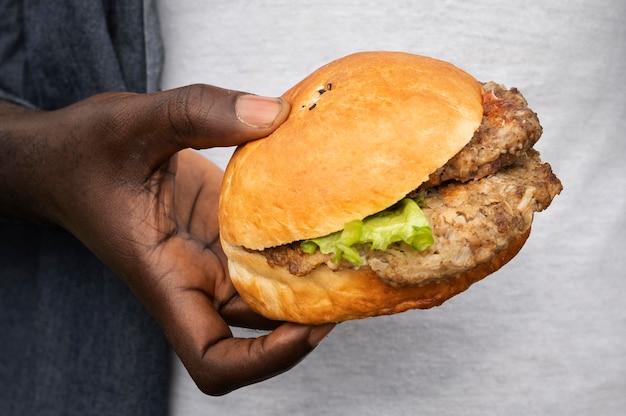 Zbliżenie dłoni trzymającej smacznego burgera