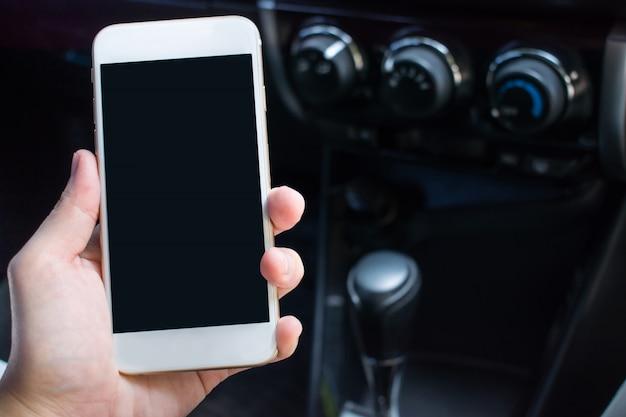 Zbliżenie dłoni trzymającej smartfon w samochodzie na podróż. z miejsca na kopię.