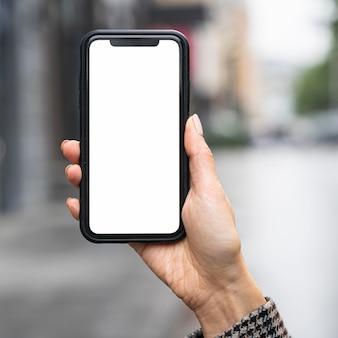 Zbliżenie dłoni trzymającej smartfon