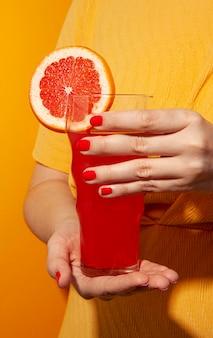 Zbliżenie dłoni trzymającej sok pomarańczowy krwi