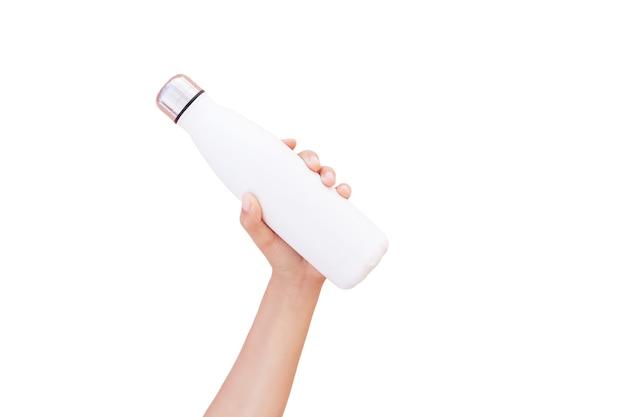 Zbliżenie dłoni trzymającej stalową butelkę wody termalnej wielokrotnego użytku z makietą, na białym tle na biały z miejsca na kopię.