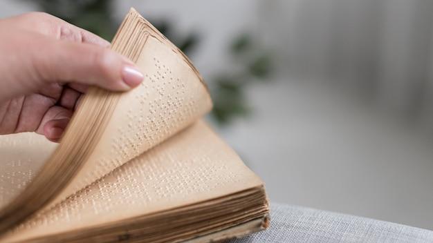 Zbliżenie dłoni trzymającej starą książkę braille'a