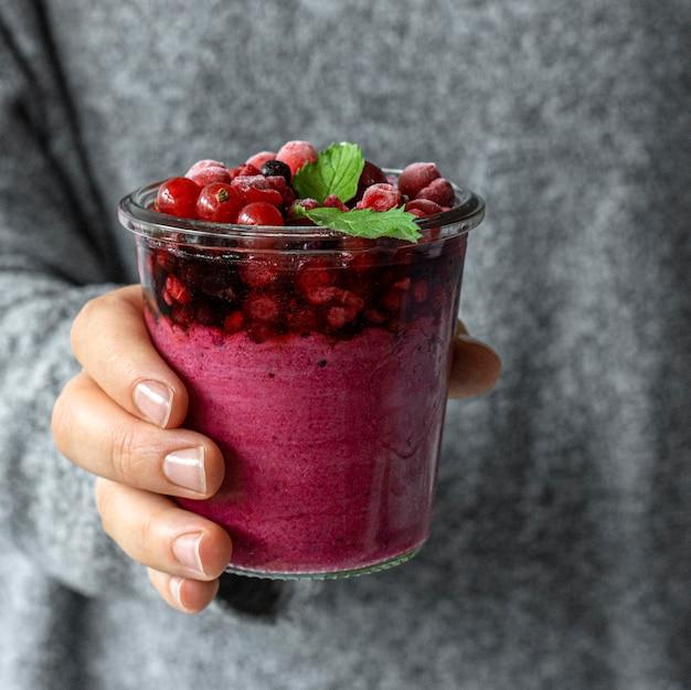 Zbliżenie dłoni trzymającej szkło owocowe smoothie
