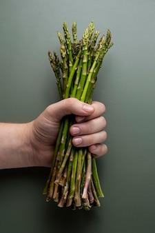Zbliżenie dłoni trzymającej szparagi