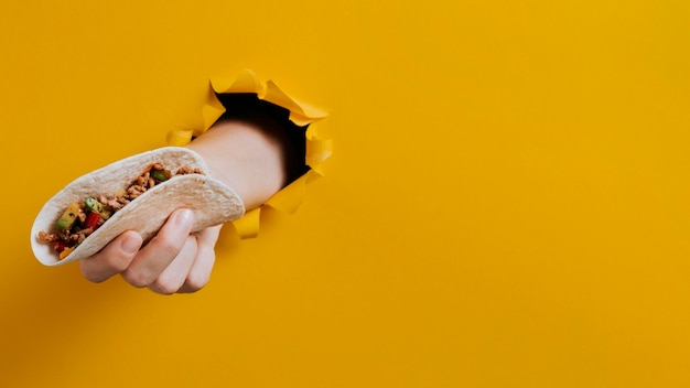 Zbliżenie dłoni trzymającej taco z kopiowaniem przestrzeni