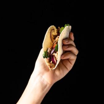 Zbliżenie dłoni trzymającej taco z mięsem