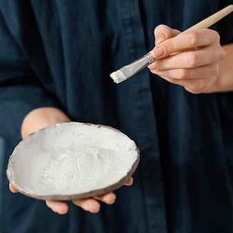 Zbliżenie dłoni trzymającej talerz i pędzel