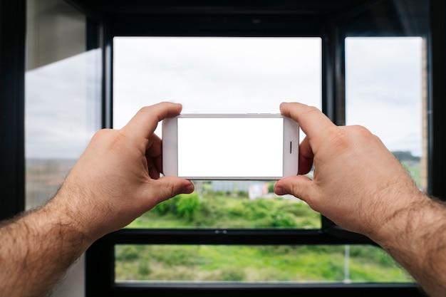 Zbliżenie dłoni trzymającej telefon komórkowy, aby zrobić zdjęcie z okna domu