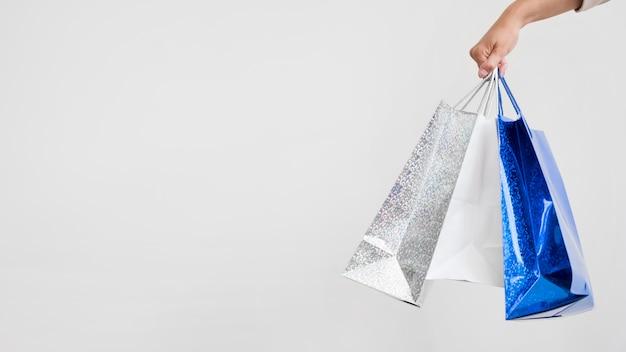 Zbliżenie dłoni trzymającej torby na zakupy z miejsca na kopię