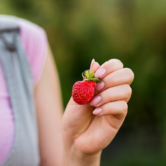 Zbliżenie dłoni trzymającej truskawkę