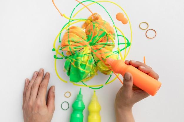 Zbliżenie dłoni trzymającej tubkę z farbą