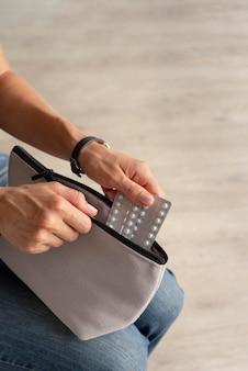 Zbliżenie dłoni trzymających folie na tabletki i kosmetyczkę