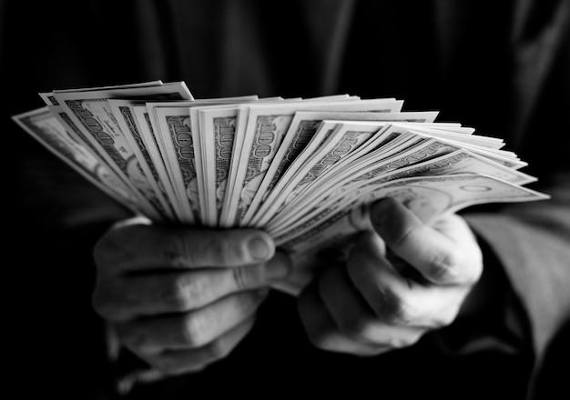 Zbliżenie dłoni trzymających gotówkę