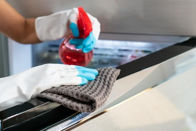 Zbliżenie dłoni w gumowych rękawiczkach z detergentem do czyszczenia w sprayu