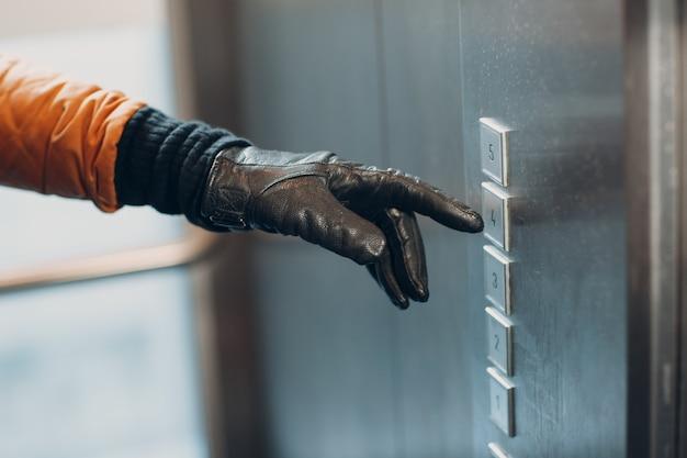 Zbliżenie dłoni w rękawiczce palcem wskazującym naciskającym przycisk windy podczas pandemii koronawirusa covid-19 koncepcji kwarantanny
