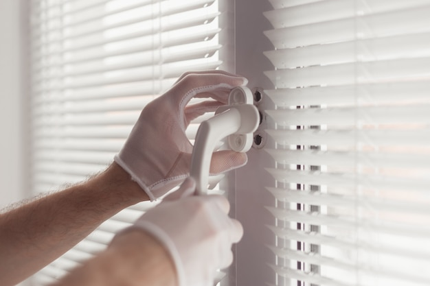 Zbliżenie dłoni w rękawiczkach ze śrubokrętem, instalowanie nowego uchwytu.
