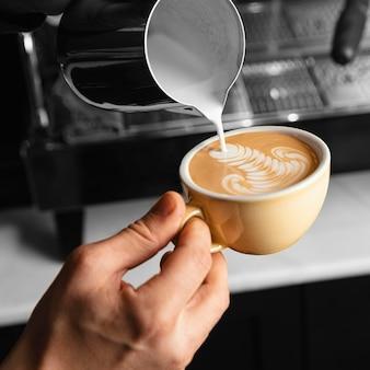 Zbliżenie dłoni wlewając mleko do filiżanki kawy
