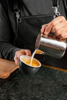Zbliżenie dłoni wlewając mleko do filiżanki