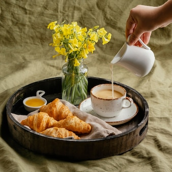 Zbliżenie dłoni wlewając mleko do kawy