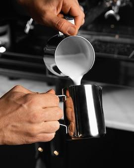 Zbliżenie dłoni wlewając mleko