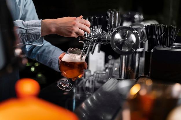 Zbliżenie dłoni wlewając piwo w szkle