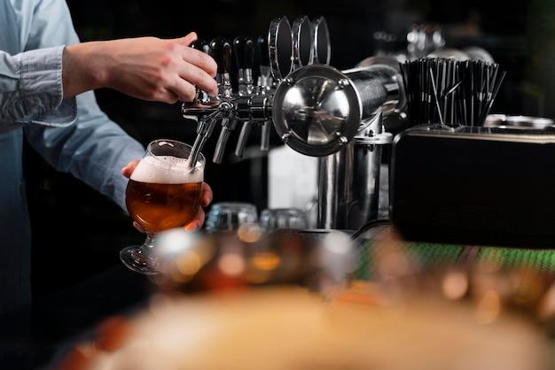 Zbliżenie dłoni wlewania piwa
