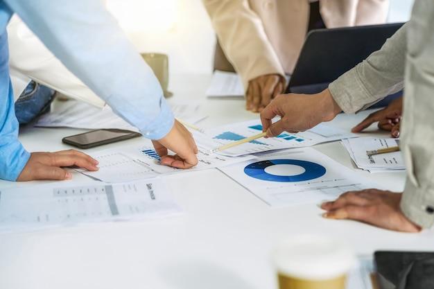 Zbliżenie dłoni współpracowników zespołu biznesowego pracujących i omawiających z różnymi dokumentami