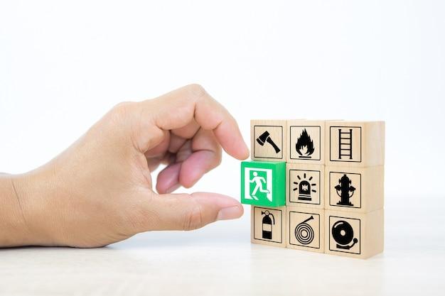 Zbliżenie dłoni wybiera drewniane klocki ułożone w stos z ikoną wyjścia drzwi.
