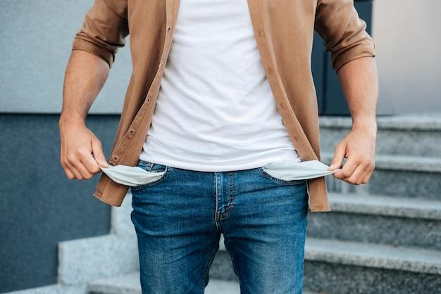 Zbliżenie dłoni wyciągających kieszenie dżinsów