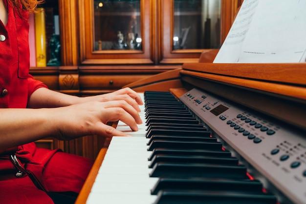 Zbliżenie dłoni wykonawcy muzyki grającej na pianinie