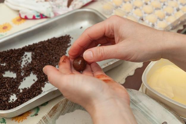 Zbliżenie dłoni wykonujących pyszne i tradycyjne brazylijskie cukierki o nazwie brigadeiro w brazylijskim portugalskim.
