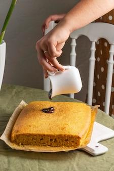 Zbliżenie dłoni wylewanie czekolady na ciasto