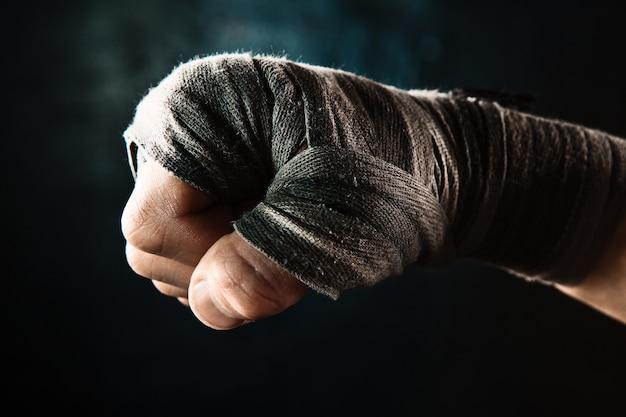 Zbliżenie dłoni z bandażem muskularnego mężczyzny trenującego kickboxing na czarno