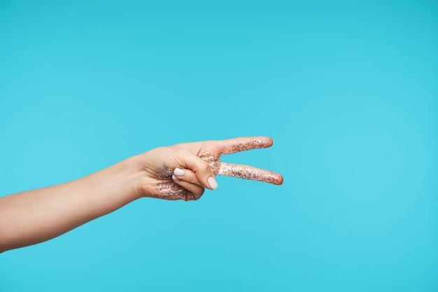 Zbliżenie dłoni z dwoma palcami w górę w geście pokoju
