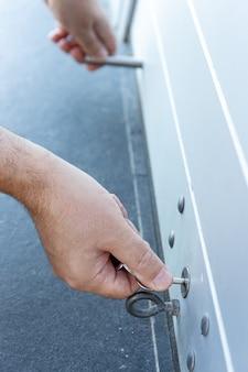 Zbliżenie dłoni z kluczem zamykającym drzwi roletowe sklepu. koncepcja zamknięcia