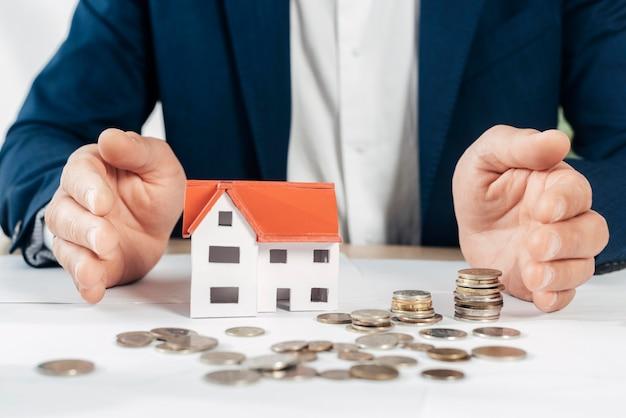 Zbliżenie dłoni z monetami i domem