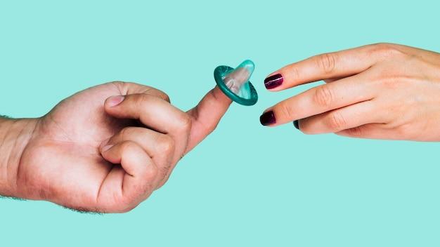 Zbliżenie dłoni z nieopakowanym zielonym prezerwatywą