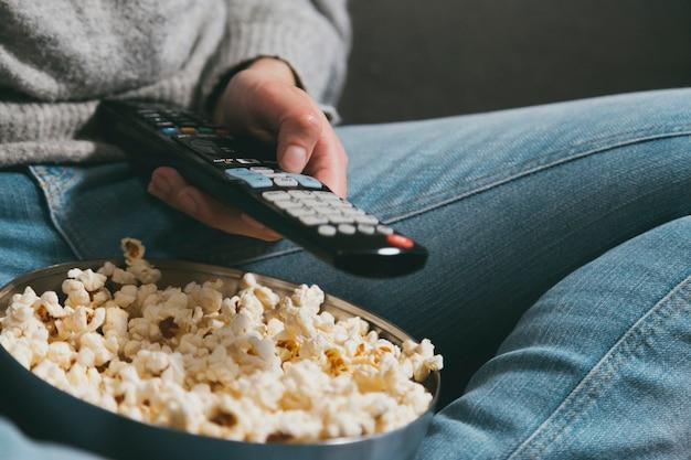 Zbliżenie dłoni z pilotem do telewizora i popcornem. noc filmowa w domu