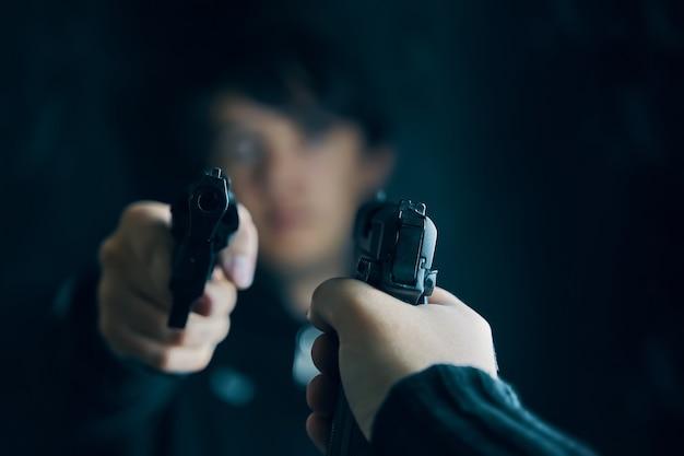 Zbliżenie dłoni z pistoletem dwóch mężczyzn celuje w siebie pistoletami strzelanina przestępców z rewolwerami da...