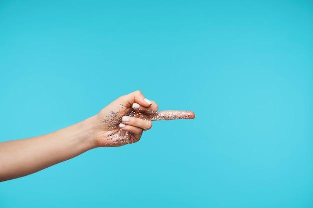 Zbliżenie dłoni z podniesionym brokatem, wskazującym na bok odsłoniętym środkowym palcem