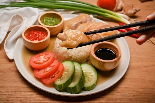 Zbliżenie dłoni za pomocą pałeczek do zaciśnięcia kurczaka w talerzu ryżowym z kurczaka hajnańskiego