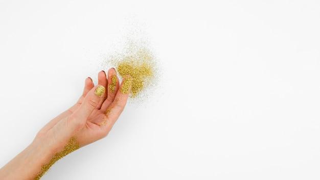 Zbliżenie dłoni ze złotym brokatem