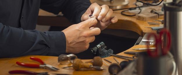 Zbliżenie dłoni złotnika zdobiącej szlachetny pierścionek z pięknymi diamentami. profesjonalny jubiler przy użyciu specjalnego sprzętu. koncepcja produkcji złotej biżuterii