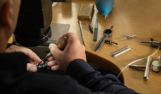Zbliżenie dłoni złotnika zdobiącej szlachetny pierścionek z pięknymi kamieniami szlachetnymi. profesjonalny jubiler patrzący na gotowy złoty pierścionek. koncepcja produkcji złotej biżuterii.
