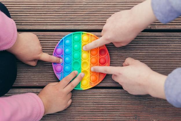 Zbliżenie dłonie dwoje dzieci, brat i siostra, chłopiec i dziewczynka grają w antystresową grę pop it