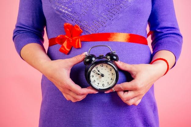 Zbliżenie dłonie kobiety w ciąży w fioletowej sukience i czerwonej satynowej kokardce na brzuchu, trzymającej budzik w studio na różowym tle. czas na koncepcję urodzenia.