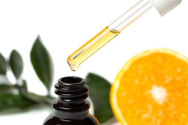 Zbliżenie do zakraplacza na brązowej butelce z pomarańczowymi liśćmi i pomarańczą w tle. selektywna ostrość.
